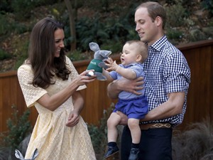 "FILE - This is a Sunday, April 20, 2014 file photo of Britain's Kate, the Duchess of Cambridge, and her husband Prince William as they give their son Prince George a stuffed toy of Australian animal called a Bilby, which has been named after the young prince, during a visit to Sydney's Taronga Zoo, Australia. Prince George turns 1 on Tuesday. While he may be too young to appreciate it, the milestone is causing a nationwide frenzy. Editorial writers call him a symbol of hope, newspaper headlines hail him as ""Gorgeous George"" and one published a 24-page glossy magazine chronicling his first 12 months. (AP Photo/David Gray, Pool, File)"