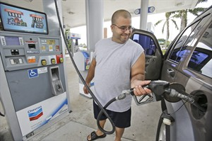 In this Wednesday, June 4, 2014 photo, Baltazar Rosado, of Hollywood, Fla., pumps gasoline into his car at a Chevron gasoline station in Pembroke Pines, Fla. The Labor Department reports on U.S. consumer prices in June on Tuesday, July 22, 2014. (AP Photo/Wilfredo Lee)