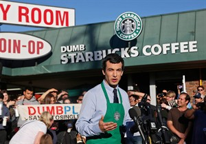"FILE - In this Feb. 10, 2014 file photo, Canadian comedian Nathan Fielder of the Comedy Central show ""Nathan For You"" comes forward as the brainchild of ""Dumb Starbucks,"" a parody store that resembles a Starbucks with a green awning and mermaid logo, but with the word ""Dumb"" attached above the Starbucks sign. Fielder who came up with the fake-store concept will discuss its origins and aftermath on the Tuesday, July 29, 2014, episode of Comedy Central's ""Nathan For You."" (AP Photo/file)"