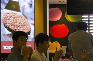 Customers enjoy their meal near an advertisement claiming to use 100 percent beef at a McDonald's restaurant in Beijing Tuesday, July 22, 2014. China's food safety agency on Tuesday announced a nationwide inspection of processing factories and meat suppliers used by a company accused of selling expired beef and chicken to McDonald's and KFC. (AP Photo/Ng Han Guan)