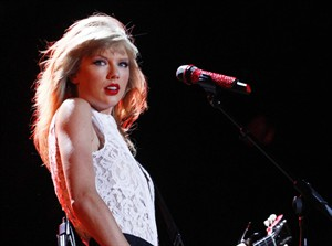 FILE - In this June 6, 2013 file photo, Taylor Swift performs at the 2013 CMA Music Festival in Nashville, Tenn. Swift, Coldplay and One Direction are part of the star-studded lineup for this year's iHeartRadio Music Festival, Clear Channel announced Wednesday, July 23, 2014. (Photo by Wade Payne/Invision/AP, File)
