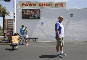 Randy Renfro, right, and others have their picture taken at the Gold & Silver Pawn Shop in Las Vegas Monday, July 28, 2014, in Las Vegas. Rick Harrison, owner of the pawn shop and one of the stars of the reality television series Pawn Stars, has proposed building a shopping plaza on land nearby. (AP Photo/John Locher)