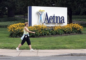 FILE - In this July 31, 2008 file photo, a woman strides past the Hartford, Conn., headquarters of Aetna, Inc. Health insurer Aetna Inc. reports quarterly financial results on Tuesday, July 29, 2014. (AP Photo/Bob Child, File)