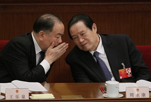 In this photo taken Friday, March 9, 2012, Zhou Yongkang, right, then Chinese Communist Party Politburo Standing Committee member in charge of security, listens to Wang Lequan, deputy chairman of the party's Political and Legislative Affairs Committee, during a plenary session of the National People's Congress at the Great Hall of the People in Beijing, China. China's Communist Party says it has launched an investigation into a former domestic security chief who was once among the country's most feared leaders. The official Xinhua News Agency cited the party as saying Tuesday, July 29, 2014 it is investigating Zhou for serious violations of party discipline, but did not provide details. (AP Photo/Ng Han Guan)