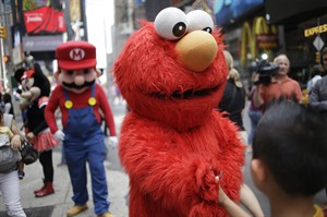 "A person dressed as Elmo shakes hands with a pedestrian in Times Square on Monday, July 28, 2014 in New York. New York City Mayor Bill de Blasio said Monday that he believes the people wearing character costumes in Times Square should be licensed and regulated. Dozens of people dressed as kids' favorites like Elmo, Cookie Monster and Batman stand near 42nd Street and pose for photos with tourists in exchange for money. De Blasio said the practice has ""gone too far."" A man dressed as Spider-man was arrested Saturday, July 28, 2014, after punching a police officer who told him to stop harassing tourists. The City Council is working on legislation that would require the characters to get a city-approved license. (AP Photo/Seth Wenig)"