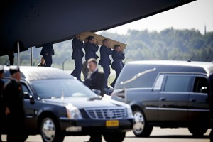 Pallbearers carry a coffin out of a military transport plane during a ceremony to mark the return of the first bodies, of passengers and crew killed in the downing of Malaysia Airlines Flight 17, from Ukraine at Eindhoven military air base, Netherlands, Wednesday, July 23, 2014. After being removed from the planes, the bodies were taken in a convoy of hearses to a military barracks in the central city of Hilversum, where forensic experts will begin the painstaking task of identifying the bodies and returning them to their loved ones. (AP Photo/Phil Nijhuis)