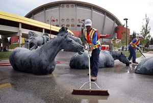 Clean-up crews work at getting the Calgary Stampede grounds ready in Calgary, Alta., Monday, June 24, 2013. The fact that organizers managed to pull off the 2013 instalment of the Calgary Stampede is cited as one of the massive achievements of Alberta's recovery from last year's flooding. THE CANADIAN PRESS/Jeff McIntosh
