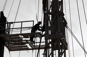 An oil worker connects pipes on a new oil rig Jan. 14, 2014, in the Persian Gulf desert oil field of Sakhir, Bahrain. THE CANADIAN PRESS/AP, Hasan Jamali