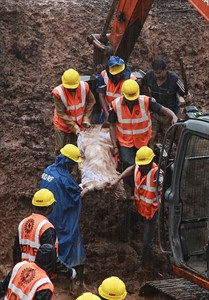 Rescue workers carry the body of a victim after a massive landslide in Malin village in Pune district of western Maharashtra state, India, Thursday, July 31, 2014. Two days of torrential rains triggered the landslide early Wednesday, killing more than two dozen people and trapping more than 150, authorities said. (AP Photo/Rafiq Maqbool)