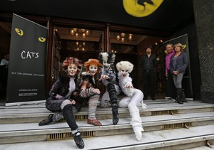 Performers in Cats costumes pose for the photographers during a photo-op to promote the return of British composer Andrew Lloyd Webber's Cats the musical return to London, Monday, July 7, 2014. British composer Andrew Lloyd Webber, 2nd right, director Trevor Nunn, 3 right, and choreographer Gillian Lynne, right, look on. The show, based on T.S Eliot's 'Old Possum's Book of Practical Cats', will return to the West End for a limited 12-week run from Dec, 2014. Cats, one of the longest-running shows in West End and on Broadway, received its world premiere in London in 1981 where it played for 21 record-breaking years and almost 9,000 performances. According to its creators Cats has been presented in over 26 countries, has been translated into 10 languages and has been seen by over 50 million people world-wide. (AP Photo/Lefteris Pitarakis)