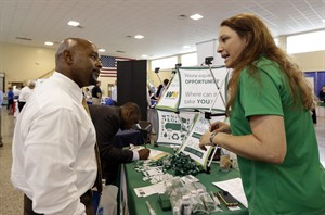 In this photo taken Wednesday, July 16, 2014, job seeker U.S. Air Force veteran Jimmie Walker, left, listens to job recruiter Desiree Akel, at a Hiring Fair For Veterans in Fort Lauderdale, Fla. The Labor Department reports the number of people who applied for unemployment benefits last week on Thursday, July 17, 2014. (AP Photo/Alan Diaz)