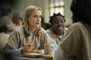 """FILE - This image released by Netflix shows Taylor Schilling, left, and Uzo Aduba in a scene from """"Orange Is the New Black."""" Netflix reports quarterly earnings on Monday, July 21, 2014. (AP Photo/Netflix, Paul Schiraldi, File)"""