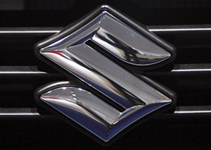 FILE - This Sept. 16 2009 file photo shows the logo of automaker Suzuki at the Frankfurt Auto Show in Frankfurt, Germany. Suzuki is recalling nearly 26,000 midsize cars in the U.S. because the daytime running light modules can overheat and could cause a fire. The recall covers the Verona from the 2004-2006 model years. It's an expansion of an earlier recall of the Forenza and Reno. (AP Photo/Daniel Roland, File)