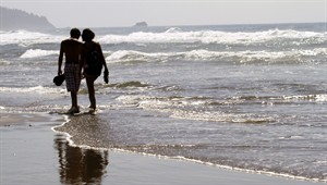 FILE - In this Aug. 26, 2010 file photo, a couple walks through the surf together in Cannon Beach, Ore. OKCupid on Monday, July 28, 2014 became the latest company to admit that it has manipulated customer data to see how users of its dating service would react to one another. (AP Photo/Don Ryan, File)