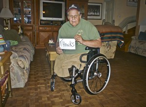 "In this July 15, 2014 photo, Michael Sulsona, a Vietnam War veteran who lost both legs to a land mine 40 years ago, poses with a ""thank you"" sign while seated in his new wheelchair at home in Staten Island, N.Y. The 62-year-old Vietnam veteran said he petitioned the VA for a new chair two years ago and received no reply. Then his wheelchair broke last week. (AP Photo/Frieda Sulsona)"