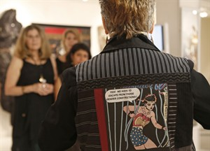 """In this July 10, 2014 photo, artist-activist Linda Stein speaks to a group of women visiting her studio in New York while wearing a """"bulleyproof"""" vest she created using Wonder Woman imagery designed to empower and protect the wearer. Stein's wearable artwork and sculptural avatars grew out of her own sense of vulnerability after the Sept. 11 terrorist attacks that occurred within blocks of her studio and living space. (AP Photo/Kathy Willens)"""