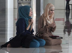 "CORRECTS CITY - Two women pray with others during a prayer session organized by former schoolmates of a cabin crew member of Malaysia Airlines Flight 17, which was shot down in Ukraine, at a mosque in Putrajaya, Malaysia Saturday, July 19, 2014. Malaysia's transport minister said the country is ""deeply concerned"" that the site in Ukraine where the Malaysia Airlines jetliner was shot down with 298 people onboard ""has not been properly secured."" (AP Photo/Satish Cheney)"