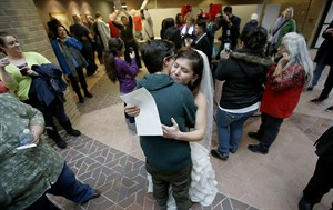 FILE - In this Dec. 23, 2013, file photo, Jax and Heather Collins embrace after getting married at the Salt Lake County Clerk's Office. Utah's decision Wednesday, July 9, 2014, to bypass asking for a review from the entire 10th U.S. Circuit Court of Appeals and go directly to the Supreme Court hastens the path to a much-anticipated review of the flashpoint issue by the highest court. Legal experts predict the court eventually will take a gay marriage case, with it happening in 2015 at the earliest. (AP Photo/The Deseret News, Ravell Call, File)