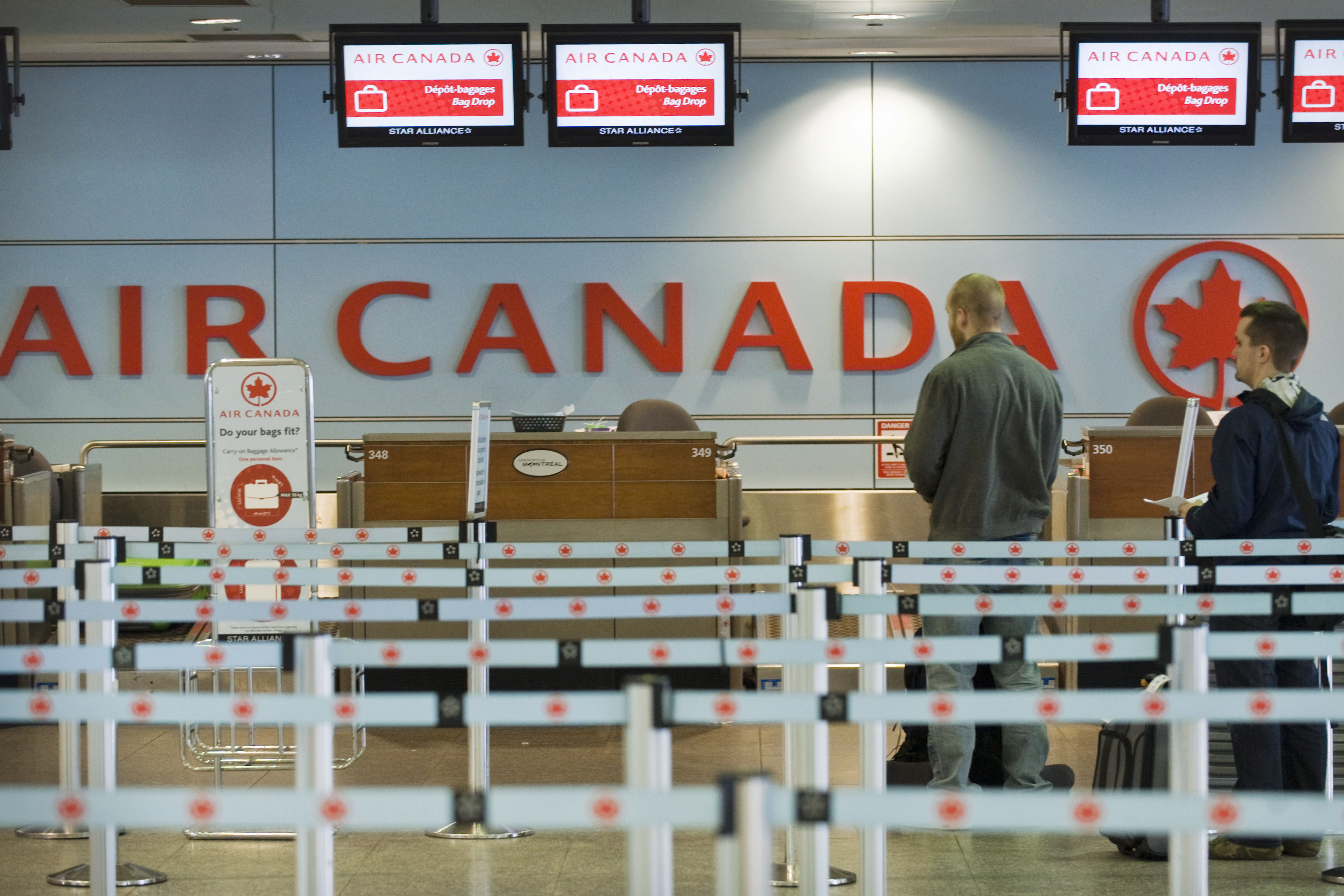 Passengers queue at an Air Canada check-in desk at Trudeau Airport in Montreal on April 13, 2012. THE CANADIAN PRESS/Graham Hughes