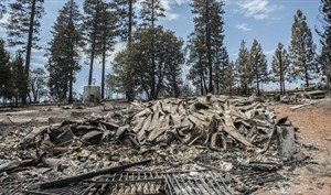 The remains of a burned home lie in the Foresta community in Yosemite National Park in California on Tuesday, July 29, 2014. Fire crews gained ground Tuesday on two of the largest wildfires in California, lifting evacuation orders for about half the homes in the path of a blaze in Yosemite and redeploying firefighters battling another fire in the Sierra Nevada foothills east of Sacramento. (AP Photo/Al Golub)