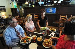 In this July 18, 2014 photo, Dawn Heigl, a waitress at The Harp, serves food at the restaurant in Wilmington, N.C. The Commerce Department reports how much U.S. consumers spent and earned in June on Friday, Aug. 1, 2014. (AP Photo/The Star-News, Matt Born)