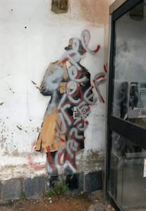 """A view of the Banksy mural which targets the issue of Government surveillance with silver and red paint sprayed over it, Cheltenham, England, Friday, Aug. 1, 2014. A mural by street artist Banksy that sparked a local preservation campaign has been defaced. """"Spy Booth"""" shows three agents in trench coats and trilby hats eavesdropping on a phone booth. It appeared in April on a wall in Cheltenham, western England, home of spy agency GCHQ. A local group formed to save the work after the building's owner attempted to have it removed and sold. Campaigner Angela De Souza said a local businessman had agreed to buy and preserve the work. But on Friday it was covered in scrawled graffiti letters. De Souza said conservators were in """"a race against time"""" to save it. Banksy works have fetched as much as $1.8 million at auction, and several of his outdoor pieces have recently been stripped from walls and sold. (AP Photo/Claire Hayhurst/PA Wire) UNITED KINGDOM OUT NO SALES NO ARCHIVE"""