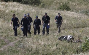 Australian experts examine the area of the Malaysia Airlines Flight 17 plane crash in the village of Hrabove, Donetsk region, eastern Ukraine Friday, Aug. 1, 2014. The head of the Dutch-led international team investigating the Malaysian Airline Flight 17 disaster says his group has retrieved additional DNA samples from 25 victims at a mortuary in Donetsk in eastern Ukraine. (AP Photo/Dmitry Lovetsky)