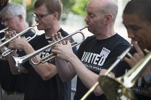 Demonstrators play their musical instruments outside Lincoln Center during a protest over a labor dispute with New York's Metropolitan Opera, Friday, Aug. 1, 2014, in New York. Metropolitan Opera says labor talks with its unions have been extended for an additional 72 hours, averting a threatened midnight lockout. The company announced late Thursday that the delay was requested by a federal mediator who had arrived just hours earlier to try to resolve the labor standoff. (AP Photo/John Minchillo)