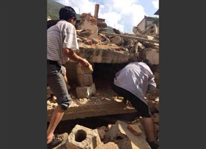 In this photo taken by cellphone and released by China's Xinhua News Agency, men at rubbles of buildings look for survivors after an earthquake in Ludian County of Zhaotong City in southwest China's Yunnan Province Sunday, Aug. 3, 2014. A strong earthquake rattled southwest China on Sunday, knocking out communication and power lines and causing people to rush out of buildings, but there were no immediate reports of injuries. (AP Photo/Xinhua/Hu Chao) NO SALES