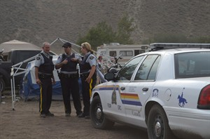 RCMP stand at the entrance to the camping area of the Boonstock Music and Art Festival in Penticton, B.C., where a 24-year-old woman from Leduc, Alberta died as the result of a drug overdose, early Saturday morning, Aug. 2, 2014. THE CANADIAN PRESS/Penticton Herald-James Miller