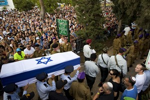 Israeli soldiers carry the coffin of Israeli Army 2nd. Lt. Hadar Goldin during his funeral at the military cemetery in the central Israeli city of Kfar Saba on Sunday, Aug. 3, 2014. Israel announced that Goldin, a 23-year-old infantry lieutenant feared captured in Gaza, was actually killed in battle. Israel had earlier said it feared he had been captured by Hamas militants Friday near Rafah in an ambush that shattered an internationally brokered cease-fire and was followed by heavy Israeli shelling that left dozens of Palestinians dead. (AP Photo/Oded Balilty)