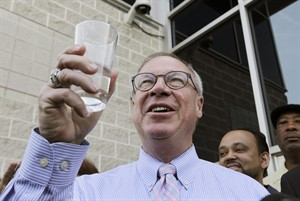 Toledo Mayor D. Michael Collins raises a glass of tap water before drinking it during a news conference in Toledo, Ohio, Monday, Aug. 4, 2014. A water ban that had hundreds of thousands of people in Ohio and Michigan scrambling for drinking water has been lifted, Collins announced Monday. (AP Photo/Paul Sancya)