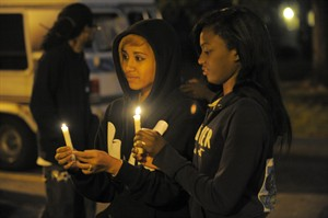 In this Wednesday, July 30, 2014 photo, Porscha Summers, 20, left, and Mykah Hall, 17, hold candles during a vigil for Jakari Pearson, who died from a gunshot wound, at the New Brewster Projects in Detroit's east side. Pearson was sleeping in his upstairs bedroom when a bullet entered through a window and struck him in the chest. (AP Photo/Detroit News, Steve Perez)