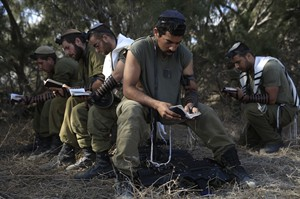 Israeli reserve soldiers pray after returning to Israel from the Gaza Strip near the Israel Gaza border, Monday, Aug. 4, 2014. A brief cease-fire declared by Israel and troop withdrawals slowed violence in the Gaza war Monday, but an attack on an Israeli bus that killed one person in Jerusalem underscored the tensions still simmering in the region as Israeli airstrikes resumed late in the day. (AP Photo/Tsafrir Abayov)