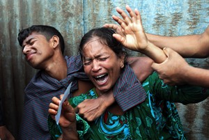 Bangladeshi woman Munni, whose daughters are missing, cries as rescuers search the River Padma after a passenger ferry capsized in Munshiganj district, Bangladesh, Monday, Aug. 4, 2014. A passenger ferry carrying hundreds of people capsized Monday in central Bangladesh, and at least 44 people either swam to safety or were rescued but the number of missing passengers is not yet known. (AP Photo/ A.M. Ahad)