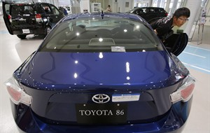A visitor checks out Toyota 86 model at Toyota showroom in Tokyo, Tuesday, Aug. 5, 2014. Toyota Motor Corp. reported a better-than-expected rise in quarterly profit as vehicle sales grew in North America and Europe, offsetting a drop in Japan. (AP Photo/Shizuo Kambayashi)
