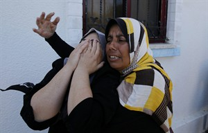 Palestinian relatives of Islamic Jihad militant Shaaban Al-Dahdouh, which was found under the rubble yesterday, grieve during his funeral in Gaza City, Wednesday, Aug. 6, 2014. (AP Photo/Hatem Moussa)