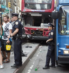 Police guard the scene of a traffic accident involving two double-decker tour buses in New York City's Theater District, Tuesday Aug. 5, 2014. The Fire Department of New York says 11 people suffered injuries from the accident, three of them seriously, but none of the injuries are believed to be life-threatening. (AP Photo/Bebeto Matthews)