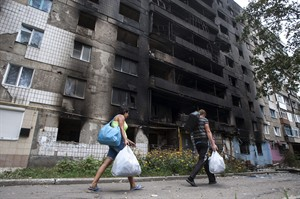 Local residents walk past a damaged building after shelling, during a fighting between pro-Russian rebels and Ukrainian government forces in Shakhtarsk, Donetsk region, eastern Ukraine, Thursday, Aug. 7, 2014. (AP Photo/Evgeniy Maloletka)