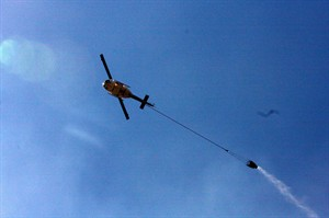Helicopter drops water on the Rowena fire in Oregon amid high winds and dry conditions on Wednesday, Aug. 6, 2014. The Rowena fire began in brush Tuesday night. (AP Photo/The Oregonian, Stuart Tomlinson)