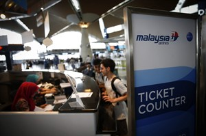 Passengers stand in front of information desk at Kuala Lumpur International Airport in Sepang, Malaysia, Friday, Aug. 8, 2014. Malaysia's state investment company said Friday it plans to make Malaysia Airlines fully government owned, removing it from the country's stock exchange before carrying out a far-reaching overhaul of the carrier that is reeling from double disasters. (AP Photo/Vincent Thian)