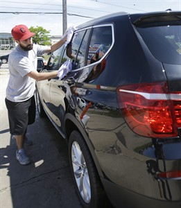 In this Friday, June 6, 2014 photo, Anthony Scharf dries a car at a car wash in Woodmere Village, Ohio. The Labor Department releases second-quarter productivity data on Friday, Aug. 8, 2014. (AP Photo/Tony Dejak)
