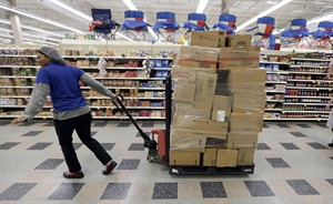 In this June 17, 2014 photo, a stocker rolls product to restock at a Kroger grocery store in Richardson, Texas. The Commerce Department releases wholesale trade inventories for June on Friday, Aug. 8, 2014. (AP Photo/LM Otero)