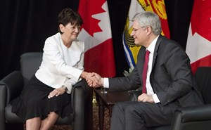 Prime Minister Stephen Harper, right, shakes hands with Jocelyne Roy-Vienneau, right, the new lieutenant governor of New Brunswick, at a news conference in Edmundston, N.B., on Friday, Aug. 8, 2014 . THE CANADIAN PRESS/Clement Allard