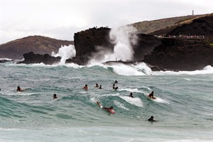 Surfers and body boarders fight for waves at Sandy Beach Park, Friday, Aug. 8, 2014, in Honolulu. High surf is expected in some spots on Oahu due to Tropical Storm Iselle. (AP Photo/Marco Garcia)