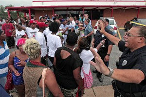 Ferguson police officers try to calm down a crowd near the scene where 18-year-old Michael Brown was fatally shot by police in Ferguson, Mo., near St. Louis on Saturday, Aug. 9, 2014. A spokesman with the St. Louis County Police Department confirmed a Ferguson police officer shot the man. The spokesman didn't give the reason for the shooting, nor provide the officer's name or race. (AP Photo/St. Louis Post-Dispatch, Huy Mach)