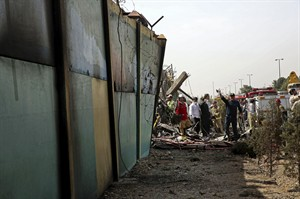 Iranian security and rescue personnel inspect the site of a passenger plane crash near the capital Tehran, Iran, Sunday, Aug. 10, 2014. An Iranian passenger plane crashed Sunday while taking off from an airport near the capital, killing tens of people onboard, state media reported. (AP Photo/Vahid Salemi)