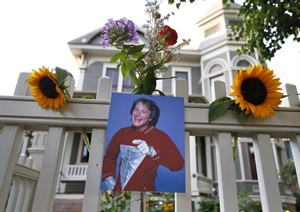 """A photo of the late actor Robin Williams as Mork from Ork hangs with flowers left by people paying their respects, in Boulder, Colo., Monday Aug. 11, 2014, at the home where his hit 80's TV series """"Mork & Mindy"""", was set. Williams, the Academy Award winner and comic supernova whose explosions of pop culture riffs and impressions dazzled audiences for decades and made him a gleamy-eyed laureate for the Information Age, died Monday in an apparent suicide. He was 63. (AP Photo/Brennan Linsley)"""