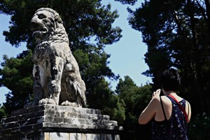 A tourist takes a picture of a 4th century BC marble Lion of Amphipolis, some 5 kilometers from a large funeral mound currently under excavation by Greek archaeologists that Prime Minister Antonis Samaras visited on Tuesday, Aug. 12, 2014. Excavators of the mound, which is believed to contain a significant grave dating to the end of Alexander the Great's reign, believe this lion originally formed part of a tomb monument that crowned the artificial hill. In the past, the lion, that was discovered a century ago, has been associated with Laomedon of Mytilene, one of Alexander's military commanders who, after the king's death in 323 B.C., became governor of Syria. (AP Photo/Alexandros Michailidis)