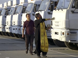 In this image taken from video a Russian Orthodox Church clergyman blesses a convoy of white trucks with humanitarian aid in Alabino, outside Moscow Tuesday, Aug. 12, 2014. The convoy of 280 Russian trucks headed for eastern Ukraine early Tuesday, one day after agreement was reached on an international humanitarian relief mission. But the international Red Cross, which is due to coordinate the operation, said it had no information on what the trucks were carrying or where they were going. (AP Photo/RTR, via Associated Press Television) TV OUT RUSSIA OUT